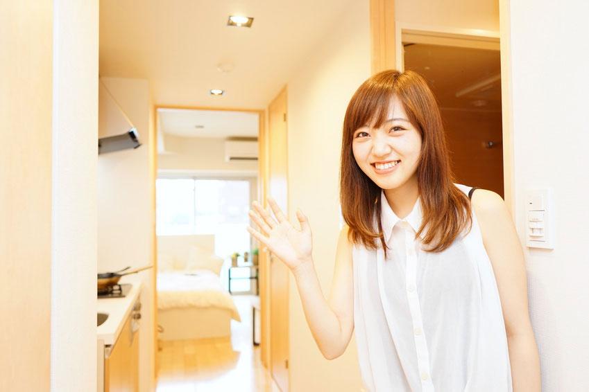 一人暮らしの部屋にお客さんを招き入れる若い女性 大