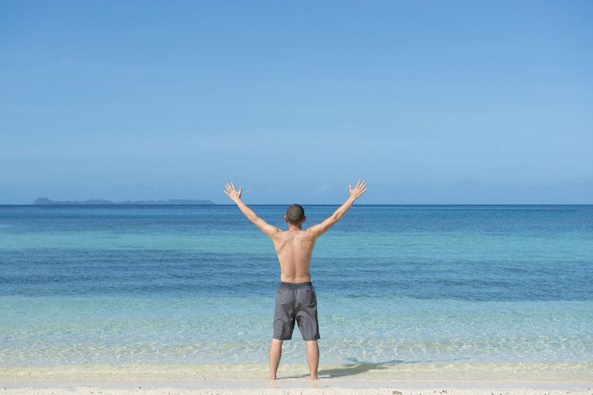 ビーチで両手を上げる男性 大